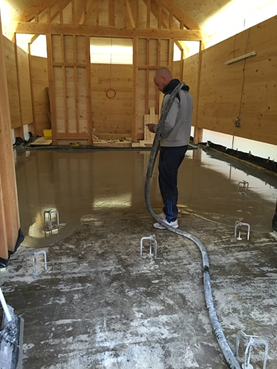 man pumping screed in wooden house