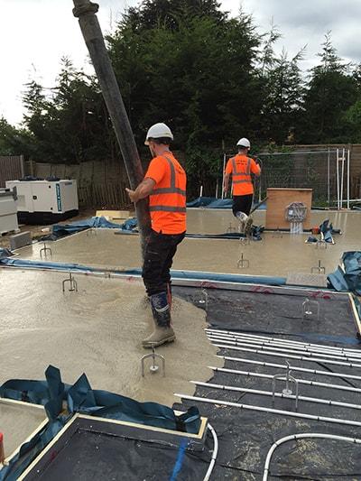 construction worker in hard hat pumping screed outside